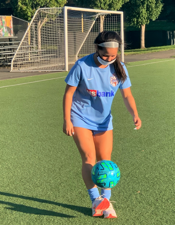 """Liv-e to play: Liv Teves (11) juggles a soccer ball while wearing a mask after practicing at Starfire Sports in Tukwila. """"Practices have definitely changed since we started back up again after COVID, but I'm glad to be back out on the field with my team,"""" teammate Kaitlyn Keyes (12) said."""
